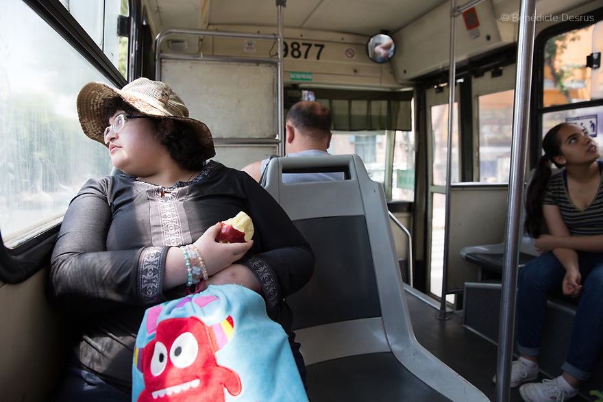 Citlalli eats an apple while riding a public bus in Mexico City, Mexico on March 26, 2017. Delia Citlalli Pineda Corzo, a 21-year-old Mexican girl, lives with her 42-year-old mother Diana Cristina Corzo Zárate in a two-room apartment in Mexico City. She was diagnosed with Prader-Willi syndrome at age four. At age 15, doctors detected that she had diabetes. Citlalli weighs 106 kilos (233.6 pounds) and stands 150 centimeters (4 feet 11 inches). She has a BMI of 50.5, making her morbidly obese. She also suffers from sleep apnea. Citlalli lacks the faculty of speech and cannot read, but her mother says they have developed their own form of communication. Prader-Willi Syndrome (PWS) is a rare genetic disorder caused by an abnormality in chromosome 15. In newborns symptoms include weak muscle tone (hypotonia), poor appetite and slow development. In childhood the person experiences a sensation of constant hunger no matter how much he/she eats which often leads to obesity and Type 2 diabetes. There may also be mild to moderate intellectual impairment and behavioral problems. Physical characteristics include a narrow forehead, small hands and feet, short in stature, and light skin color. Prader-Willi syndrome has no known cure. However, with early diagnosis and treatment such as growth hormone therapy, the condition may improve. Strict food supervision is typically required. PWS affects an estimated 1 in 10,000 to 30,000 people worldwide. (Photo by Bénédicte Desrus)