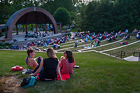 Three women sit at the top of the hill to listen to an outdoor concert at the ampitheater in Alum Creek Park in Westerville as part of a summer concert series.