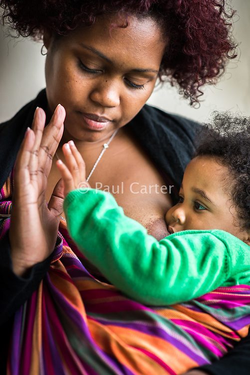 A mother touches hands with her 15 month old toddler breastfeeding in a sling in a cafe.<br /> <br /> 18/10/12<br /> Harrow, England, UK