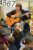 Teacher plays a guitar in a nursery class at Christ Church Bentinck Church of England Primary School, Westminster, London.