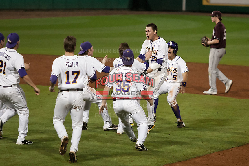 The LSU Tigers mob JaCoby Jones #23 after he drove in the winning run in the bottom of the 10th inning against the Mississippi State Bulldogs during the NCAA baseball game on March 16, 2012 at Alex Box Stadium in Baton Rouge, Louisiana. LSU defeated Mississippi State 3-2 in 10 innings. (Andrew Woolley / Four Seam Images).