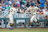 Michigan Wolverines first baseman Jimmy Kerr (15) is congratulated by third base coach Nick Schnabel (23) after hitting home run in the seventh inning against the Vanderbilt Commodores during Game 1 of the NCAA College World Series Finals on June 24, 2019 at TD Ameritrade Park in Omaha, Nebraska. Michigan defeated Vanderbilt 7-4. (Andrew Woolley/Four Seam Images)