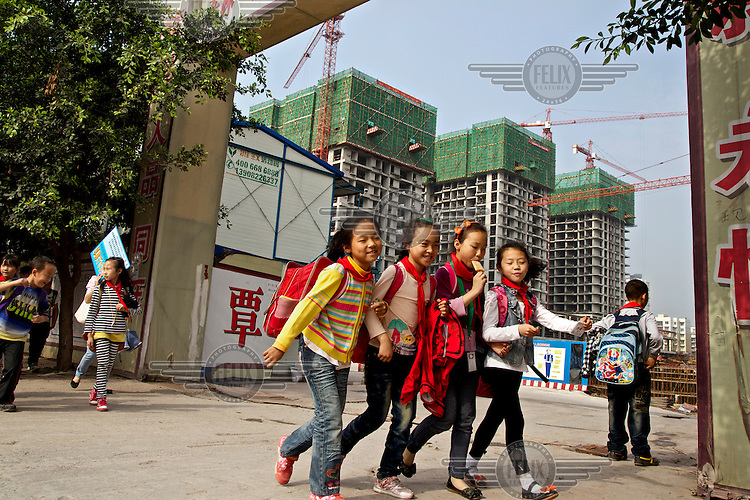 Children leave school for home at a housing project in the southwestern Chinese megapolis of Chongqing. They were all moved from their farmland and resettled nearby in this purpose-built estate. The Chinese government plans to move 250 million rural residents into urban areas over the coming dozen years though it is unclear whether people want to move and where the money for this project will come from. Further urbanisation is meant to drive up consumption to counterbalance an export orientated economy and end subsistence farming but the drive to get people off the land is causing tens of thousands of protests each year. /Felix Features