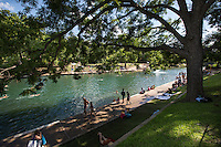 Barton Springs Pool is a shady grove of live oak trees dating back to the 1800s providing a natural spot for a quiet place to rest from the hot Texas sun.
