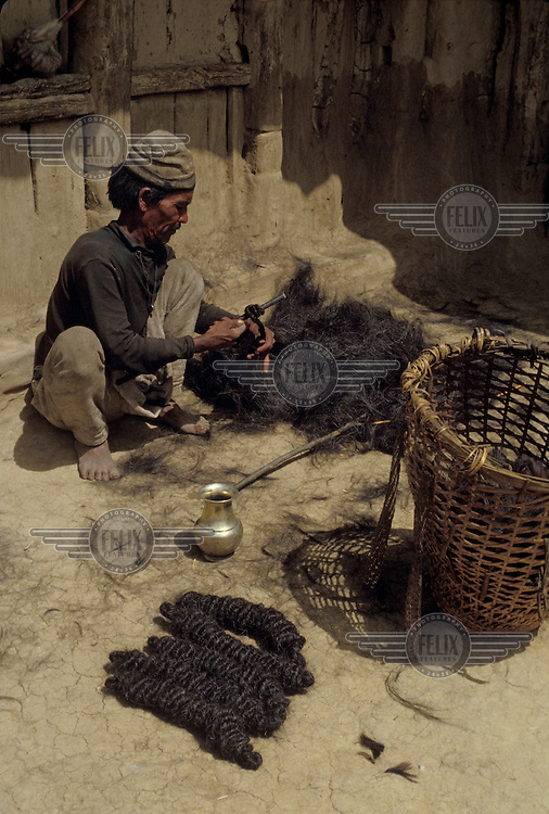 A villager preparing goat hair yarn for weaving into rugs.
