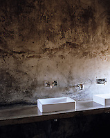 A row of sinks sit against one varnished concrete wall in the large communal children's bathroom