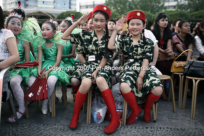 KURLE, CHINA - JUNE 13: Unidentified school children waits to perform in a school competition at an outdoor stage on June 13, 2007 in central Kurle, China. Hundreds of children competed in different genres such as traditional dance, singing and acting.    .(Photo by Per-Anders Pettersson)....