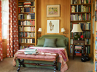 The guest room features wood panelling and built in shelves lined with books. Red and green striped fabrics cover the bed and seat.