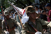 People dressed in pacific War era military uniforms parade carrying flags and replica weapons during the commemoration of the end of the Pacific war at Yasukuni Shrine, Kudanshita, Tokyo, Japan. August 15th 2010