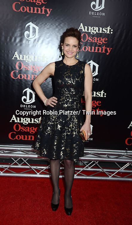 "Carla Gugino in Carolina Herrera gold and black dress attends the New York Premiere of ""August: Osage County"" on December 12, 2013 at the Ziegfeld Theatre in New York City."