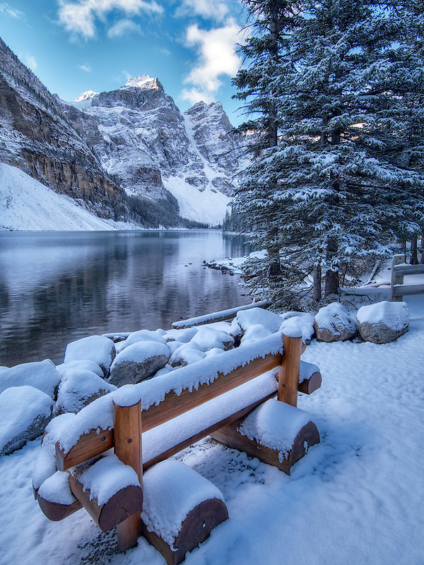 Bench with First snow of the season on Moraine Lake. Banff National Park, Alberta, Canada