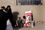 4 APRIL 2012, Kabul, Afghanistan: Women and their children with sacks of food distribution flour  at Qala-e-Fato village on the outskirts of Kabul.  Picture by Graham Crouch/The Australian