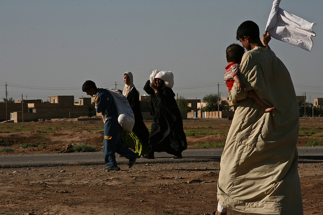 A man in Baqubah, Iraq carries a white flag identifying his family as civilians, as they carry bags of rice and flour distributed by U.S. and Iraqi forces to residents caught in fighting during a large-scale offensive to clear al Qaida and other fighters from the city. June 25, 2007. DREW BROWN/STARS AND STRIPES