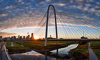 In this vertical pano view of the Margaret Hunt Hill Bridge after sunrise as the sun peep through the bridge with a sun burst  and these lovely clouds over the cityscape.  This was one of the three bridge of the Trinity Project. The sunburst reflects in the Trinity river at the Hunt Bridge as the day begins in downtown Dallas.  You can also see the Margaret McDermott bridge in the distance, along with the Reunion Tower, Bank of America,Fountain Place and many other high rise buildings in the city.