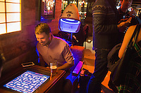 Emily Benotti (not pictured) and Jason Lowell play a free Ms. Pac-Man machine at Hojoko, a Japanese bar and restaurant in The Verb Hotel in the Fenway neighborhood of Boston, Massachusetts, USA, on Friday, Dec. 4, 2015.