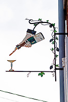 A wrought iron painted sign that illustrates the theme of champagne and wine production: a hand holding a wine bottle pouring champagne into a coupe champagne glass, the village of Hautvillers in Vallee de la Marne, Champagne, Marne, Ardennes, France