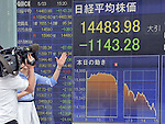 May 23, 2013, Tokyo, Japan - A local TV crew shoots the stock price board for an afternoon news show as Japan stock prices plunged 7.3 percent, the biggest one-day drop in 13 years, on the Tokyo Stock Exchange market  on Thursday, May 23, 2013. The Nikkei ended at 14,483.98, 1,143.28 points lower in the 11th-largest point drop on record.  (Photo by Natsuki Sakai/AFLO)