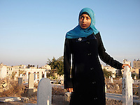 "Amira Al-Qerem (16) visits the grave of her father, sister and brother in Gaza City on October 26 2010. Amira was missing and presumed dead after she was injured by one of the same explosions that killed her father, brother and sister during the last days of the Israeli invasion of Gaza in 2009. She was found three days later, after her family thought they had buried her remains with those of the other three. She is one of the main subjects of the controversial documentary film ""Tears of Gaza"" by director Vibeke Løkkeberg."