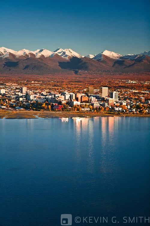 Aerial view of Anchorage, looking to the east with the Chugach Mountain Range behind it, fall foliage, sunset, Anchorage, Alaska, USA.