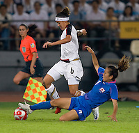 USWNT forward (6) Natasha Kai steps through the tackle of Japanese defender (4) Azusa Iwashimizu while playing at Worker's Stadium.  The USWNT defeated Japan, 4-2, during the semi-finals of the Beijing 2008 Olympics in Beijing, China.