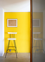 A bright yellow wall in the corridor of this apartment makes a simple yet stunning statement