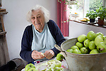 Woman in kitchen peeling bowl of cooking apples