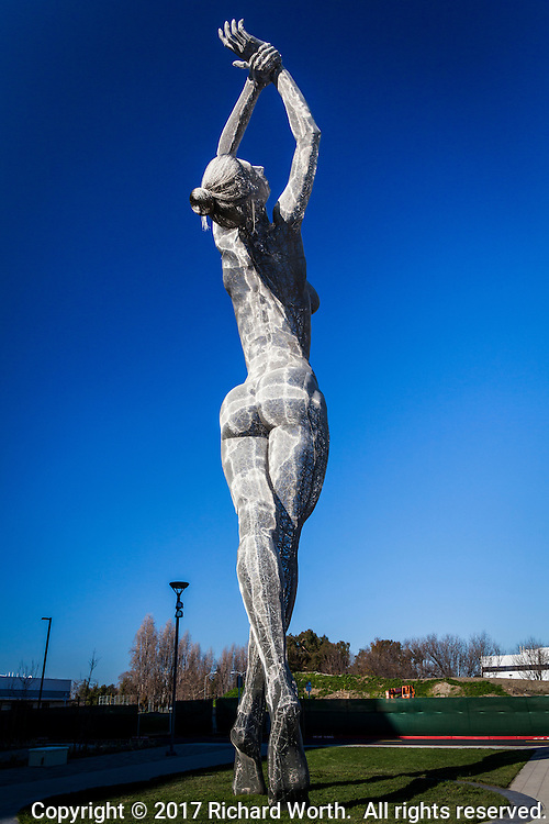 'Truth is Beauty' sculpture with arms raised into a clear, blue sky at the San Leandro Tech Campus, San Leandro, California.