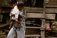 Boy flies a balloon as his mother runs from the rain. Kapangan, Benguet. February, 2001