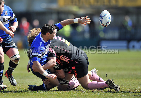 Stephen Donald offloads the ball after being tackled. Amlin Challenge Cup quarter-final, between Bath Rugby and Stade Francais on April 6, 2013 at the Recreation Ground in Bath, England. Photo by: Patrick Khachfe / Onside Images