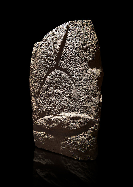Late European Neolithic prehistoric Menhir standing stone with carvings on its face side. The representation of a stylalised male figure starts at the top with a long nose from which 2 eyebrows arch around the top of the stone. below this is a carving of a falling figure with head at the bottom and 2 curved arms encircling a body above. at the bottom is a carving of a dagger running horizontally across the menhir. Excavated from Cabamadau, Villa Sant' Antonia. Menhir Museum, Museo della Statuaria Prehistorica in Sardegna, Museum of Prehoistoric Sardinian Statues, Palazzo Aymerich, Laconi, Sardinia, Italy. Black background.