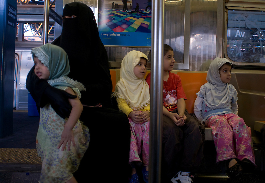 A muslim falmily return from the beach. Subway riders. Street photography in NY August 4, 2007