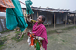 Rozina Biswas hangs laundry in Suihari in northern Bangladesh. Devastating floods in August 2017 affected thousands of families across the region. Biswas' house was almost entirely covered with water, and she lost chickens, ducks, cash, and her identity documents to the flood waters. Christian Aid and the Christian Commission for Development Bangladesh, both members of the ACT Alliance, worked together to provide emergency food packages to vulnerable residents, including Biswas and her family.
