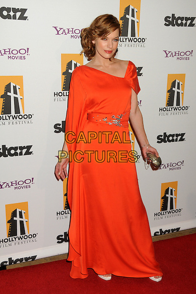 MILLA JOVOVICH.14th Annual Hollywood Awards Gala Presented By Starz held at The Beverly Hilton Hotel, Beverly Hills, CA, USA. .October 25th, 2010 .full length red orange maxi dress clutch bag silver sash waist brooch silk satin grecian one shoulder sleeve  .CAP/ADM/BP.©Byron Purvis/AdMedia/Capital Pictures