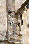 12th century stone figure of a Saint holding a book, Holy Cross church, Sherston, Wiltshire, England, UK