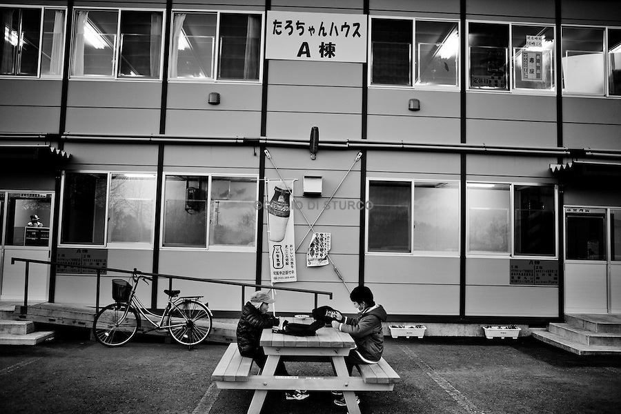 In the new Taro community  not just temporary housing  but also local amenities are provided. Here a local man wokrs in a grocery store at night, December 2011..In the north east of Japan there is a small city called Taro that was completely destroyed by the tsunami on the 3/11. After the tsunami the whole population of 8000 people moved to the top of the mountain where they settled down.  .Here they had temporary housing, temporary shops, a japanese warm bath and a temporary clinic provided by MSF. Almost one year later they are still living there, they have created their own new little community village and this has became the new reality for them. In this small colony you can find barber shops, restaurants, grocery stores, schools and a playground just like a normal village. The colony is not far from the sea so, as the majority of the population from Taro are fishermen, they don't find it too hard to survive in their new environment. From a temporary shelter this has became the new TARO Village.
