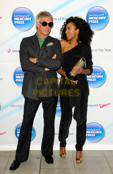 PAUL WELLER & CORINNE BAILEY RAE .attend photocall to announce the nominations for The Barclaycard Mercury Prize, The Hospital, Endell St, London, England, UK, July 20th 2010..music full length award trophy grey gray jacket  green shirt black round sunglasses pinstripe trousers one shoulder sleeve jumpsuit catsuit .CAP/CJ.©Chris Joseph/Capital Pictures.