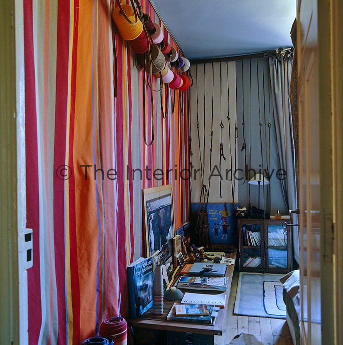 A wall of striped fabric with a row of cotton bobbins strung across it glimpsed through the open door into this bedroom