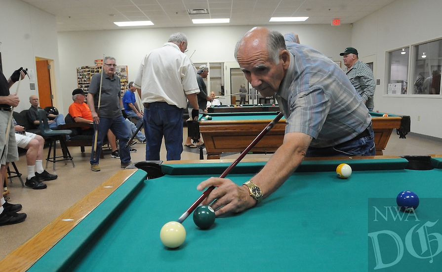 NWA Democrat-Gazette/FLIP PUTTHOFF<br /> ON CUE<br /> Ed Pennebaker lines up a shot during a game of 8-ball Tuesday July 7 2015 at the Rogers Adult Wellness Center. The pool room was a popular spot on a rainy Tuesday morning, but players said it is busy rain or shine.