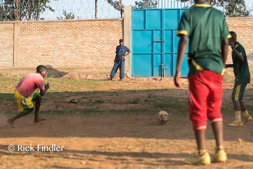 BURUNDI, Ruyigi: 10 June 2015 Ruyigi Re-education Centre Feature.<br /> See accompanying article for general information. <br /> Pictured: A police guard watches on as inmates play football. <br /> Rick Findler / Story Picture Agency