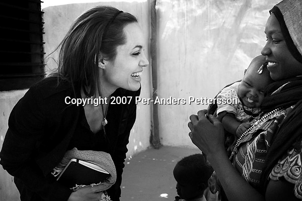 OURE CASSONI, CHAD FEBRUARY 27: Angelina Jolie, the Oscar winning actress and UNHCR Goodwill Ambassador, greets a woman and her baby in a refugee camp. Angelina Jolie spent two days visiting Oure Cassoni, a refugee camp close to the Sudan border. Almost 27,000 refugees lives there and it was opened in 2004. .(Photo by Per-Anders Pettersson/Getty Images).