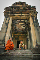 A monk and a child sat at a library structure in the grounds of Angkor Wat, Siem Reap province, Cambodia.