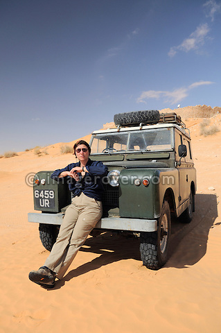 Africa, Tunisia, Ksar Rhilane. Desert tourist Doris having a rest on the front end of an historic 1962 Land Rover. In the background the old historic roman fortress (Ksar Ghilane) three kilometers to the north east of the oasis Ksar Ghilane. --- No releases available, but releases may not be needed for certain uses. Automotive trademarks are the property of the trademark holder, authorization may be needed for some uses.  --- Info: Image belongs to a series of photographs taken on a journey to southern Tunisia in North Africa in October 2010. The trip was undertaken by 10 people driving 5 historic Series Land Rover vehicles from the 1960's and 1970's. Most of the journey's time was spent in the Sahara desert, especially in the area around Douz, Tembaine, Ksar Ghilane on the eastern edge of the Grand Erg Oriental.