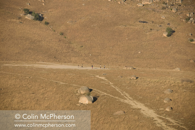 A group of children playing football on a plateau in winter in the Drakensberg mountains, north of Mbabane, Swaziland. The Kingdom of Swaziland (population 1.1m), a small, landlocked country in southern Africa was bordered by South Africa on three sides and Mozambique to the east, with Mbabane as its administrative capital. At the start of the 21st century, the country had the highest incidence per head of population of HIV/Aids in the world and and high levels of poverty mainly in rural areas where 75 per cent of the population lived.