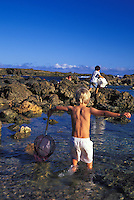 Young boys playing in tide pools at Shark's Cove, North Shore, Oahu