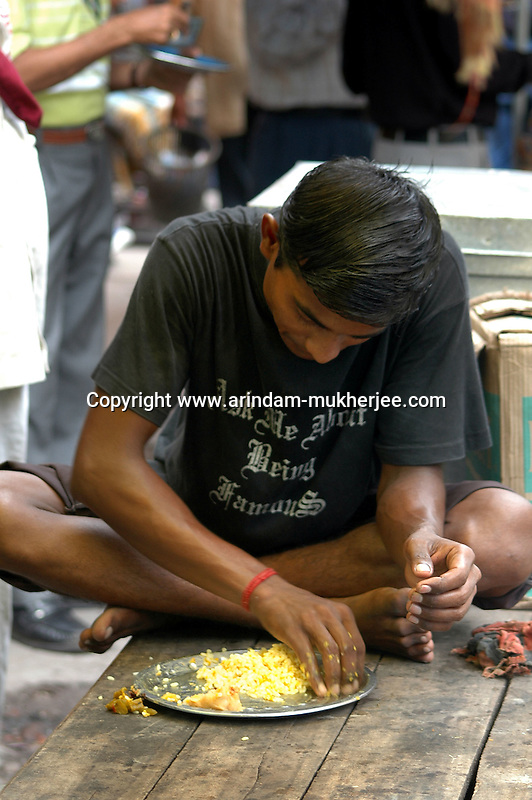 A young Indian labour having lunch during break at  a street food stall in Dalhousie area of Kolkata. Street food stalls are serving the office goers for decades. All kind of Indian foods are available on the street at an affordable price. They sale them openly. Street food stalls are another results of unempoloyment and over poppulation. They serve millions of people in India. Kolkata, West Bengal,  India  7/18/2007.  Arindam Mukherjee/Landov