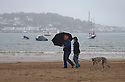 24/05/15<br /> <br /> A couple brave the rain to take their dog for a walk on Instow beach, North Devon as the bank holiday weekend weather takes a turn for the worse.<br /> <br /> All Rights Reserved - F Stop Press.  www.fstoppress.com. Tel: +44 (0)1335 418629 +44(0)7765 242650