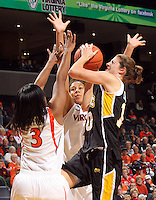 Dec. 18, 2010; Charlottesville, VA, USA; UMBC Retrievers 6-0 Meghan Colabella forward (10) is defended by Virginia Cavaliers guard Paulisha Kellum (3) and Virginia Cavaliers center Simone Egwu (4) as she shoots the ball during the game at the John Paul Jones Arena.  Mandatory Credit: Andrew Shurtleff