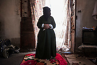 "Lebanon - Jdeideh - .Husniyah, 80-year-old, comes from the village of Nazarieh. She arrived alone, three months ago, and she is now hosted in a small two-room-house together with seven other members of her family. Without money, they are helped by some neighbours who donated them blankets and some food. ""The house is so small that we have to cook in the bathroom, but as long as I am alive, I don't care about it"", she says."