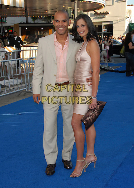 "AMAURY NOLASCO & DAYANARA TORRES.The Paramount Pictures' L.A. Premiere of ""Transformers"" held at The Mann's Village Theatre in Westwood, California, USA. .June 27th, 2007           .full length couple beige suit jacket pink shirt dress satin brown clutch purse .CAP/DVS.©Debbie VanStory/Capital Pictures"