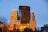 Minneapolis skyline at sunset with the Basilica, IDS Tower, Capella Tower, and Wells Fargo Tower.